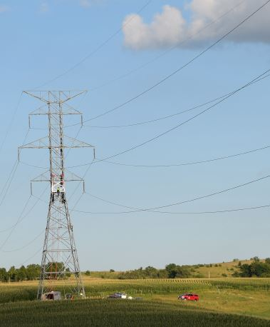 fiber optic ground wire is strung above the transmission line. Crews work on a transmission tower.