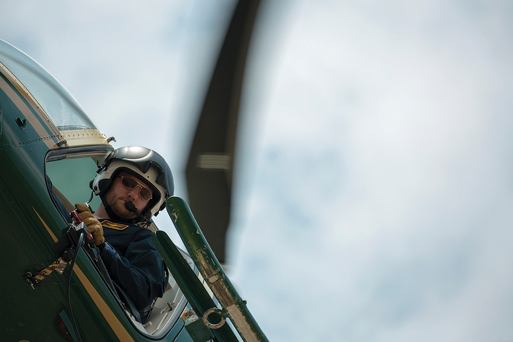 A helicopter pilot hangs his head out the window and looks down while flying above the camera