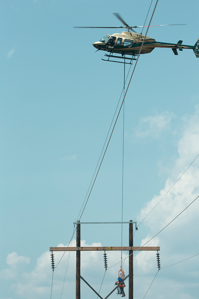 A helicopter dangles a line worker next to a transmission line to access the pole